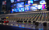 A multi channel audio mixer on a television station with shallow depth of field.