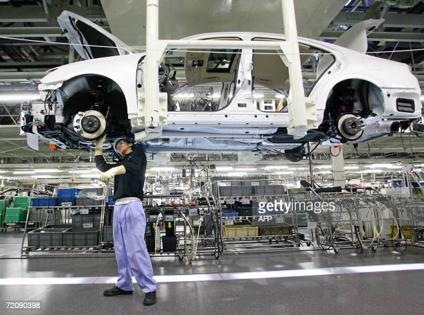 A worker at Japan's auto giant Toyota motor assemble LEXUS car at the company's plant in Miyata city Fukuoka prefecture 02 October 2006 More than...