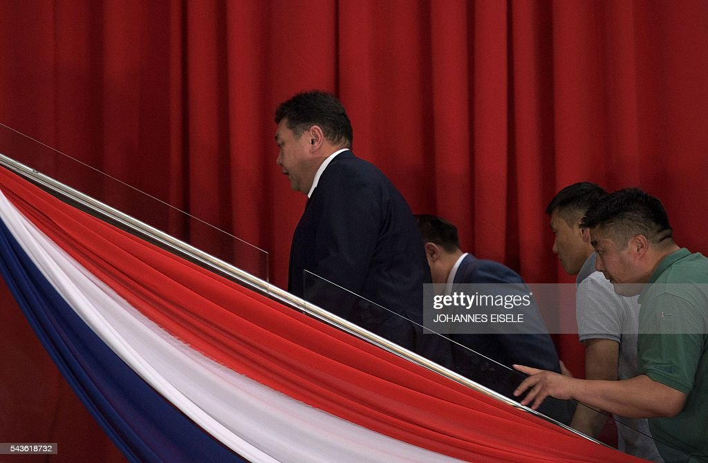 Miyegombiin Enkhbold (L), chairman of Mongolian People's Party (MPP) leaves after he spoke to the press in Ulan Bator in the night of June 30, 2016. Mongolians went to the polls across their sprawling, sparsely-populated country on June 29 as it struggles to benefit from its vast natural resources amid disputes over foreign investment and slumping demand from neighbouring China. It took Mongolian nomad Pagvajaviin Shatarbaatar seven days to get to his polling station to vote in in the general election -- accompanied by more than 2,000 sheep, goats and horses. EISELE