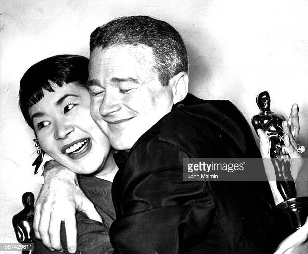 Miyoshi Umeki and Red Buttons hold fast to their Oscars as they embrace in joy over winning awards for best performances by supporting actor and...