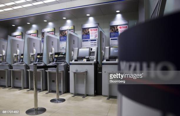 Mizuho Bank Ltd automated teller machines stand at the Mizuho Financial Group Inc headquarters in Tokyo Japan on Friday April 21 2017 Mizuho is...