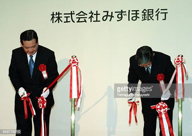 Mizuho Bank President and CEO Tadashi Kudo and Mizuho Holdings Inc President and CEO Terunobu Maeda bow during a ribboncutting ceremony to inaugurate...