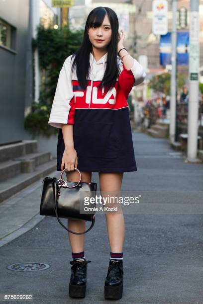 Mizuki Aihara wearing an oversized Fila red white and blue top platform black shoes with wide ribbon black laces and a leather black bag with large...