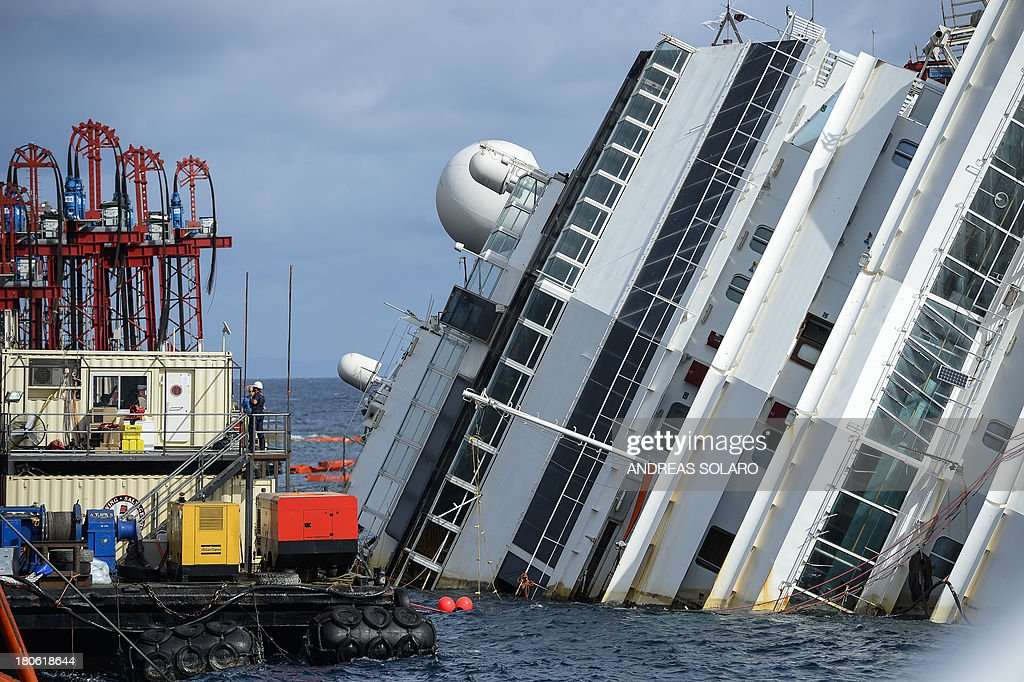 Mmembers of the US salvage company Titan and Italian firm Micoperi work at the wreck of Italy's Costa Concordia cruise ship near the harbour of Giglio Porto on September 15, 2013. Salvage workers will attempt to raise the cruise ship on September 16, 2013, weather permitting, in the largest and most expensive maritime salvage operation in history, so-called 'parbuckling', to rotated the ship by a series of cables and hydraulic machines. Thirty-two people died when the ship, with 4,200 passengers onboard, hit rocks and ran aground off the island of Giglio on January 2012.