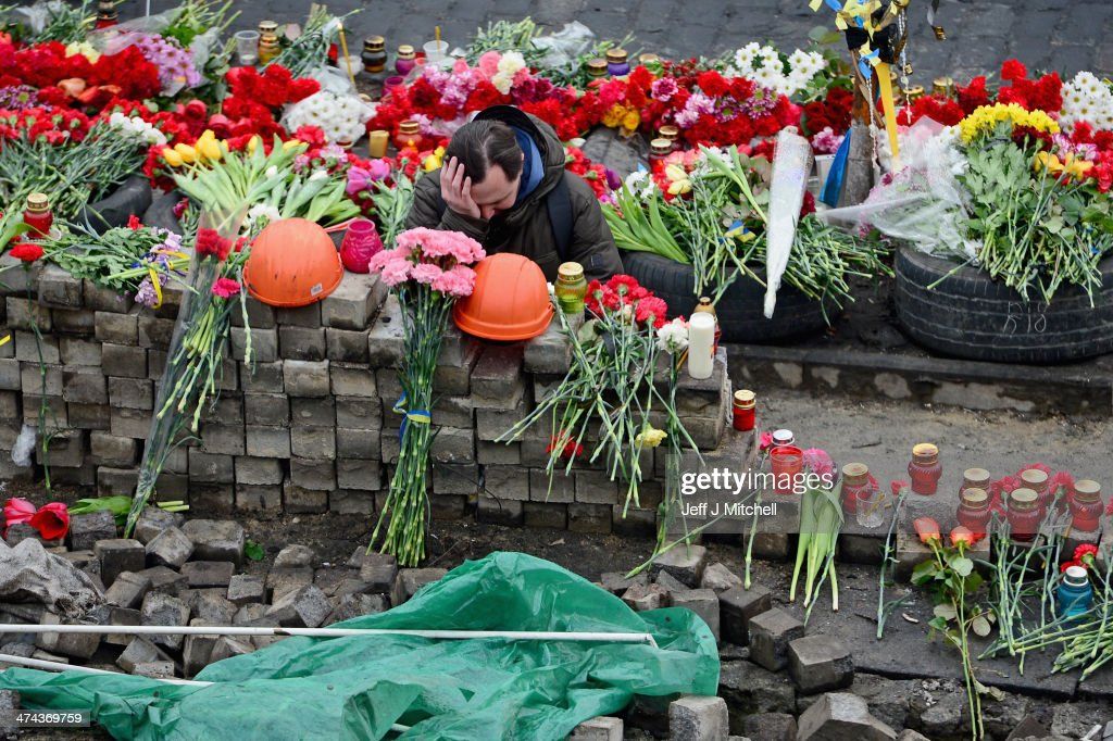 A mna reacts next to flowers left for anti-government demonstrators killed in clashes with police on February 22, 2014 in Kiev, Ukraine.Prime Minister Yanukovych is said to have left Kiev for a eastern stronghold as the country's parliament voted to remove Yanukovych from office and call for new elections.