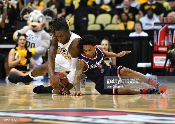 Mo AlieCox of the Virginia Commonwealth Rams dives for a loose ball alongside Khwan Fore of the Richmond Spiders during the semifinals of the...