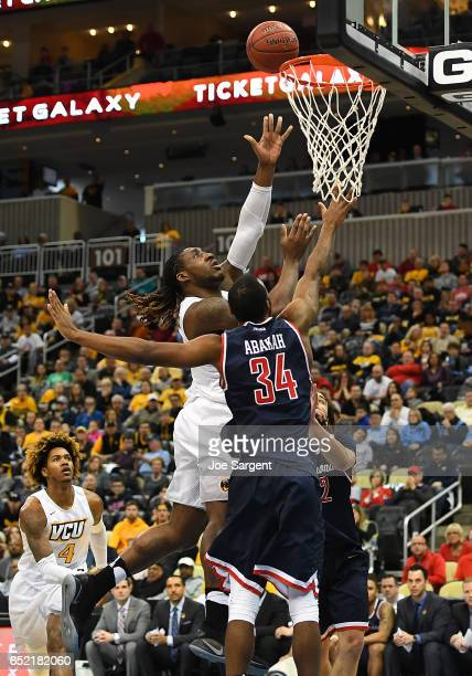 Mo AlieCox of the Virginia Commonwealth Rams drives to the hoop in front of Kwesi Abakah of the Richmond Spiders during the semifinals of the...