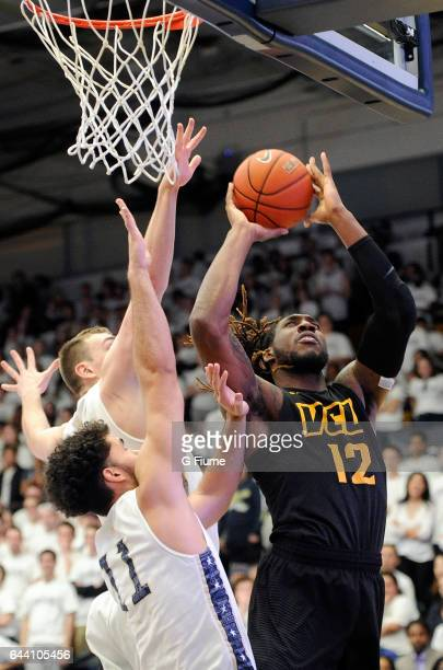 Mo AlieCox of the Virginia Commonwealth Rams drives to the hoop against the George Washington Colonials at Charles E Smith Athletic Center on...