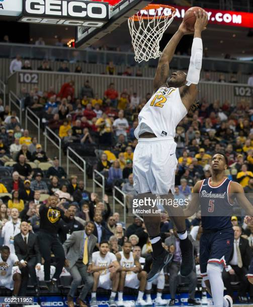Mo AlieCox of the Virginia Commonwealth Rams dunks the ball past Nick Sherod of the Richmond Spiders in the Semifinals of the men's Atlantic 10...
