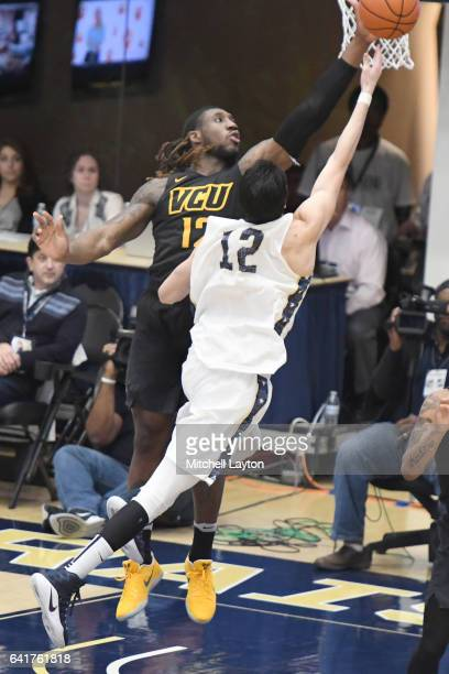 Mo AlieCox of the Virginia Commonwealth Rams tires to block shot of Yuta Watanabe of the George Washington Colonials during a college basketball game...