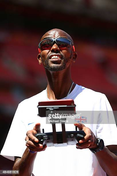 Mo Farah of Great Britain looks on as he flies a drone during a practice session ahead of the 15th IAAF World Athletics Championships Beijing 2015 at...
