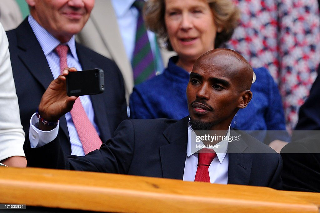 Mo Farah uses his mobile phone before the Ladies' Singles second round match between Eugenie Bouchard of Canada and Ana Ivanovic of Serbia on day three of the Wimbledon Lawn Tennis Championships at the All England Lawn Tennis and Croquet Club on June 26, 2013 in London, England.