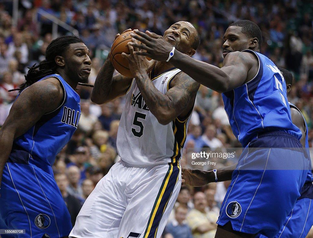Mo Williams #5 of the Utah Jazz drives between Bernard James #5 and Jae Crowder #9 of the Dallas Mavericks during the second half of an NBA game October 31, 2012 at EnergySolution Arena in Salt Lake City, Utah.