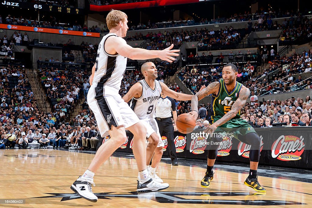 Mo Williams #5 of the Utah Jazz passes the ball against Matt Bonner #15 and Tony Parker #9 of the San Antonio Spurs on March 22, 2013 at the AT&T Center in San Antonio, Texas.