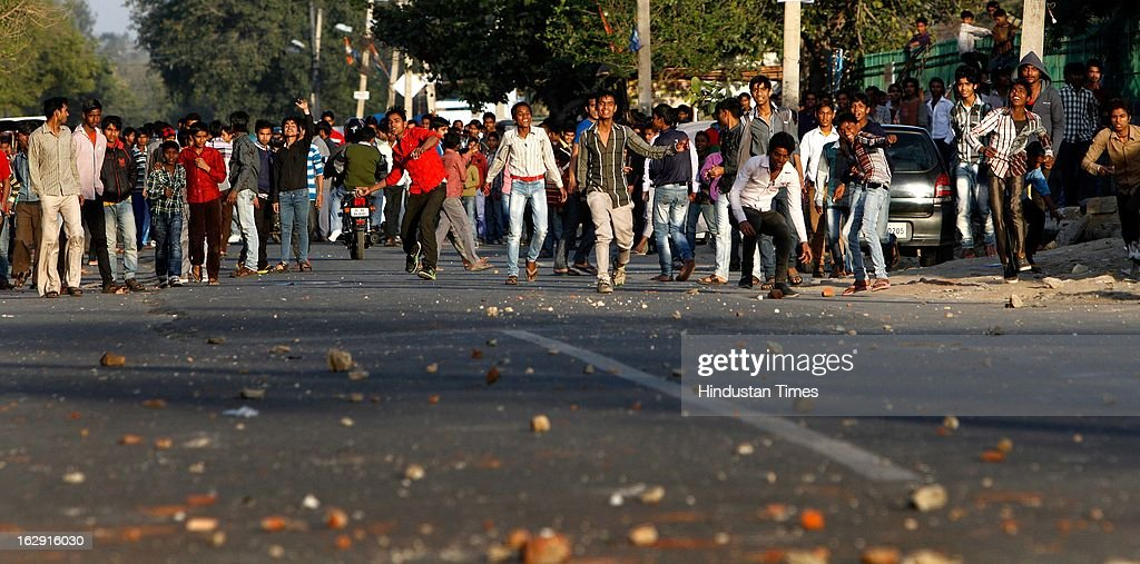A mob throwing stone on police near Sanjay Gandhi hospital during a protest after an eight-year-old girl, student of Class 2, was allegedly raped inside the premises of a North Delhi Municipal Corporation school at Mangolpuri Area on March 1, 2013 in New Delhi, India.