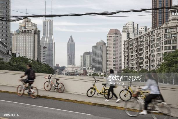 Mobike left and Ofo Inc right and second right bicycles stand parked along the sidewalk of a street in Shanghai China on Thursday May 25 2017 In...