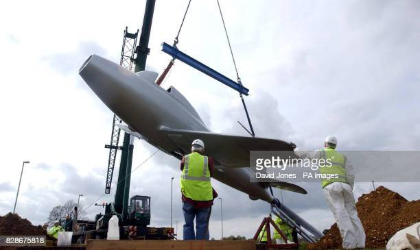 A mobile crane places a full scale replica of a jet aircraft on a traffic roundabout south of Lutterworth Leicestershire The aircraft replica is a...