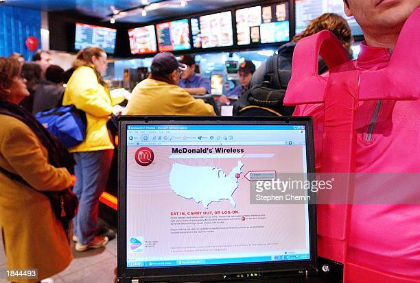 A 'mobile messenger' holds a laptop computer featuring the new wireless computer connection at a McDonald's restaurant March 12 2003 in New York City...