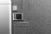 mobile phone and open slots for nano SIM cards, micro SD drive and metal key on grey background with copy space, black and white photo