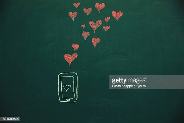 Mobile Phone And Red Heart Shape Drawing On Blackboard