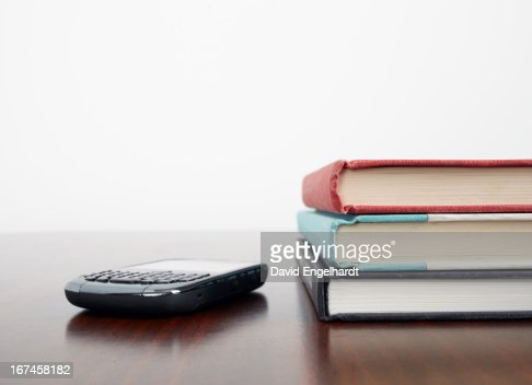 Mobile phone beside stack of books : Stock Photo