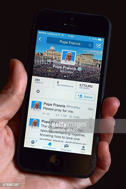 A mobile phone displays a tweet of Pope Francis reading 'Please pray for me' on his @Pontifex twitter account on March 13 2014 in Rome Pope Francis...
