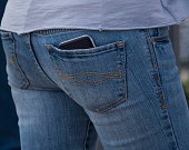 Mobile, smartphone in a blue jeans back pocket of a woman.