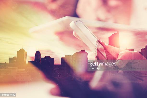 Mobile phone in hand with city skyline.