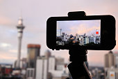 Mobile phone photographing and filming a rainbow in a rain cloud over Auckland skyline, New Zealand.