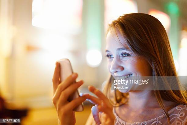 Mobile phone screen lights up smiling blonde woman's face
