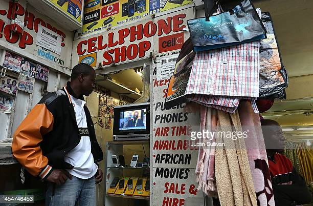 A mobile phone shop worker watches a televised broadcast of the Nelson Mandela memorial service on December 10 2013 in Johannesburg South Africa Over...