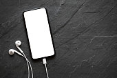 Mobile phone with empty screen and earphones on black stone surface; mock-up for your design