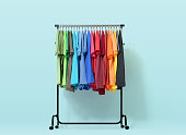 Mobile rack with color clothes on light blue background. File contains a path to isolation.