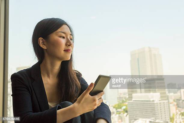 Mobile Smart Telephone Being Used By a Japanese Business Woman