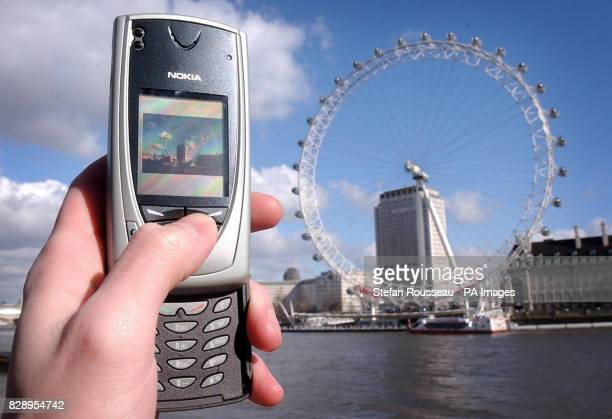 A mobile user takes a picture of the British Airways London Eye using the builtin camera on a Nokia picturemessaging phone Industry experts hope that...