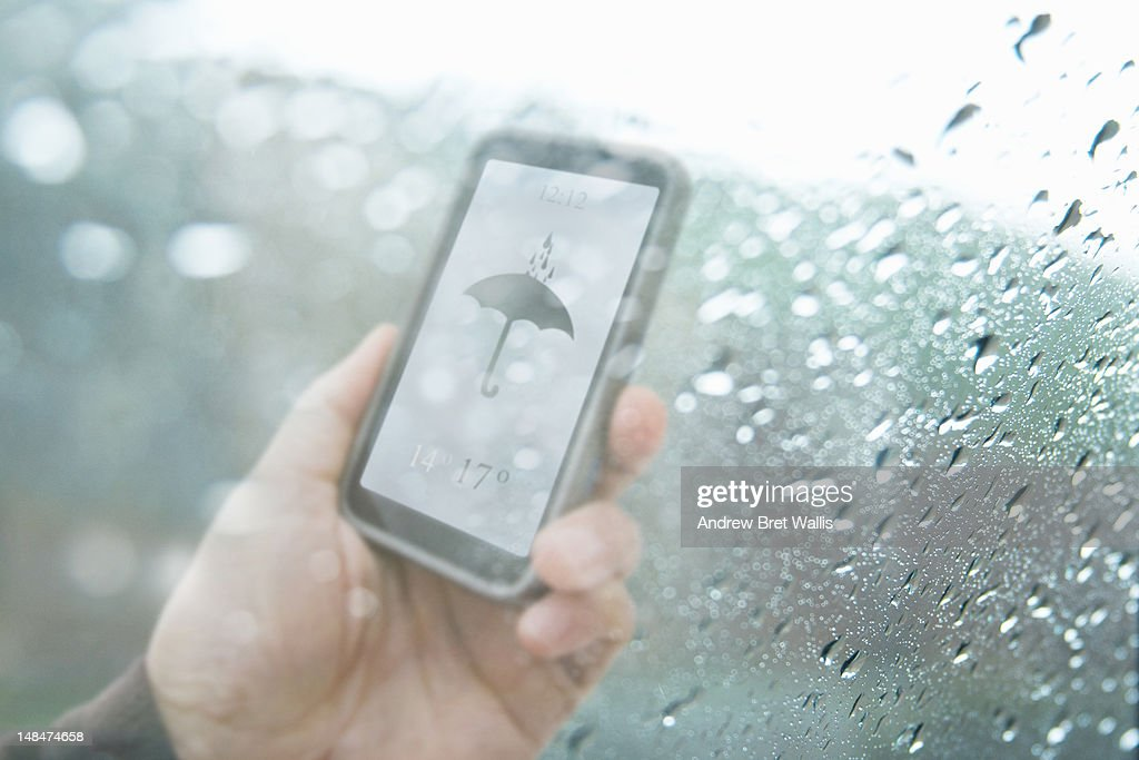 Mobile weather text behind rain soaked window : Stock Photo