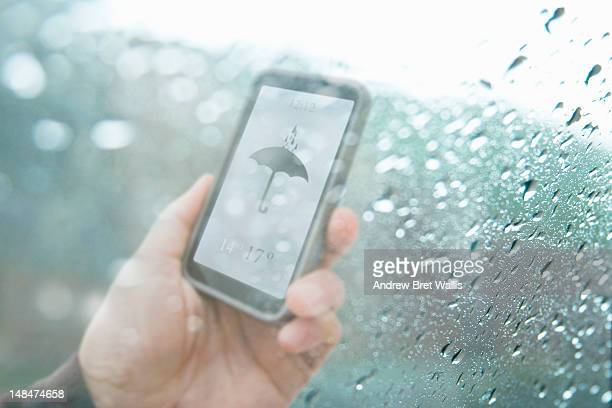 Mobile weather text behind rain soaked window