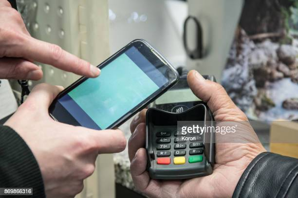 Mobile/Contactless Payment - showing to older man how it works