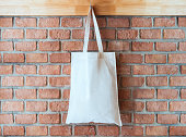 Mock up Blank Cotton Tote Bag on Brick wall Background Hipster lifestyle