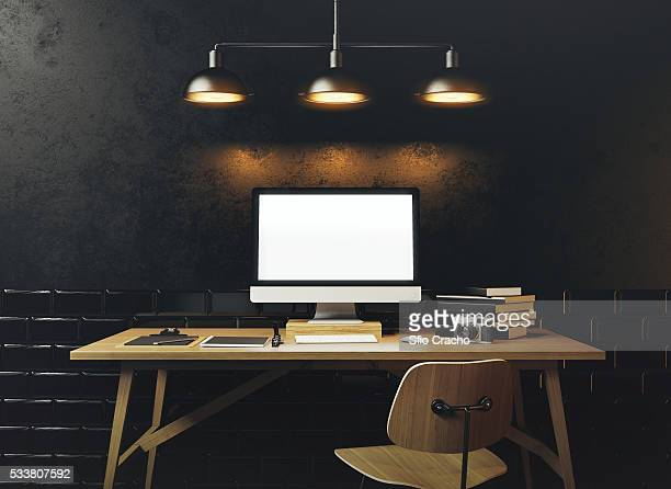 Mock up of generic design computer screen. Workspace in the black loft with vintage tiles on the wal