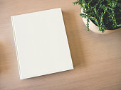 Mock up white Book cover on wooden table with Green Plant