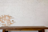 Mock up wooden table with white brick wall. For product display montage.'t
