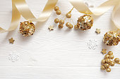 Mockup Christmas decor top view and gold ball, flatlay on a white wooden background with a ribbon, with place for your text.