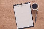 Mockup for check list, empty note pad paper with pen and coffee cup on brown wood background. Office, writer or study concept