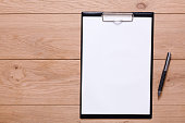Mockup for check list, empty note paper with pen on brown wood background. Office, writer or study concept