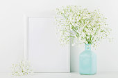 Mockup of picture frame decorated flowers in vase on white background with clean space for text and design your blogging.