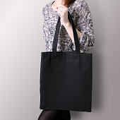 Mock-up. Girl is holding black cotton tote bag. Handmade eco shopping bag for girls.