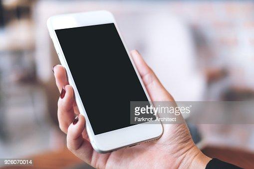 Image de la maquette d'une main tenant blanc téléphone mobile avec écran de bureau noir blanc avec arrière-plan flou : Photo