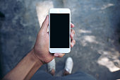 Mockup image of a man's hand holding white mobile phone with blank black screen while standing on concrete polishing floor