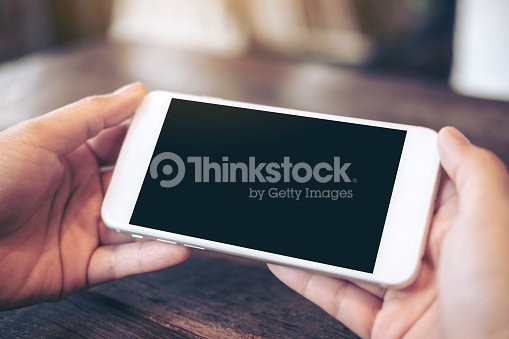 Mockup image of hands holding white mobile phone with blank black screen for watching and playing games on wooden table in cafe : Stock Photo